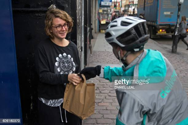 Restaurant Food Delivery company 'Deliveroo' employee Billy Shannon delivers food to a customer while working in Camden Town north London in November...