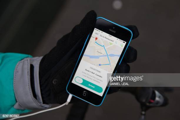 Restaurant Food Delivery company 'Deliveroo' employee Billy Shannon shows his route on his smartphone while working in Camden Town north London in...