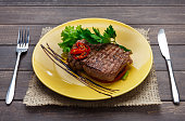 Restaurant food closeup on wood. Perfect juicy beef steak with vegetables and parsley on yellow plate with cutlery. Appetizing meat dish served with sauce, dinner meal. POV