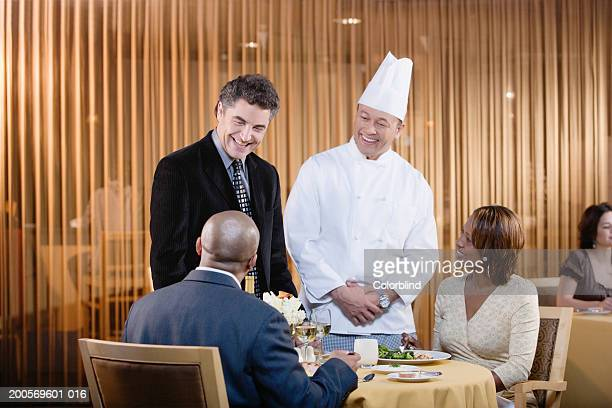 Restaurant manager and chef talking to couple at restaurant
