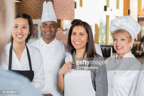 Restaurant manager giving instructions to chefs and waitstaff