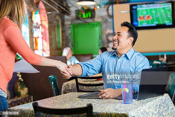 Restaurant manager shaking hands with woman before interview