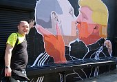 Restaurant owner Dominykas Ceckauskas pose next to a mural on the wall of his establishment depicting US Presidential hopeful Donald Trump and...