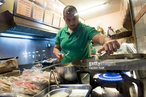 Restaurant owner Habib Hassoun prepares falafel in the restaurant at Sonnenallee in Neukoelln district on October 29 2013 in Berlin Germany According...