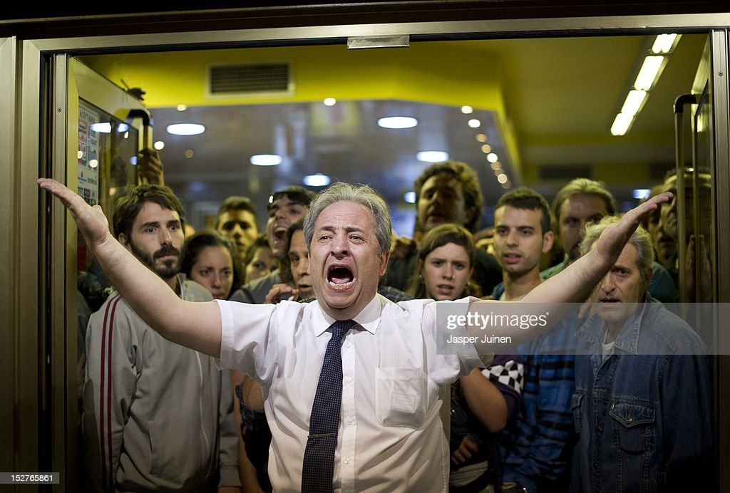 A restaurant owner shouts, with his clients behind him, at demonstrators to stop throwing stones at his restaurant, after a protest against spending cuts and the government of Mariano Rajoy ended in riots around the Spanish parliament on September 25, 2012 in Madrid, Spain. Demonstrators from various organizations, demanding a new constitutional process, are marching today from three different locations in the center of Madrid to the lower house in the Spanish parliament.