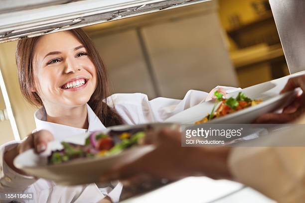 Restaurant server taking customer's food from chef