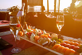 Luxury Restaurant table with sushi plate,champagne bottle  and the Barcelona beach on background. Sun flare effect .