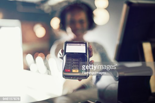 Restaurant waitress holding an electronic card payment machine : Stock Photo