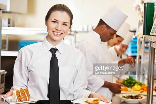 Restaurant waitress holding deserts prepared by professional chefs