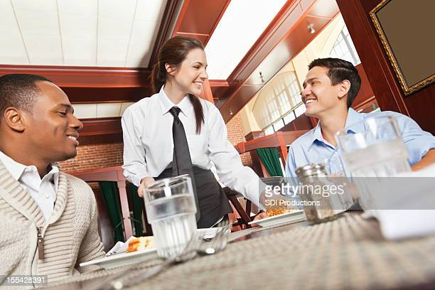 Restaurant waitress serving food to guests