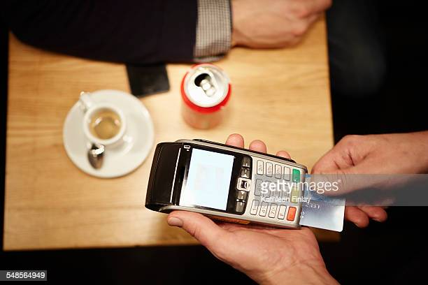 Restaurant worker inserting customers credit card into credit card reader
