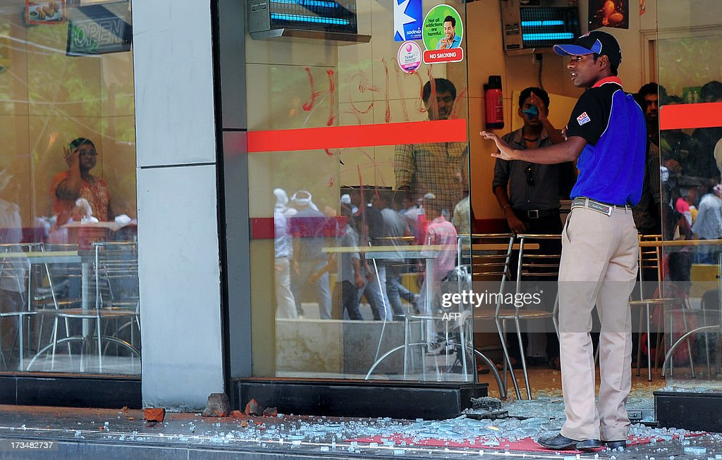 A restaurant worker stands outside a damaged restaurant during a protest against reservation for Other Backward Classes (OCC) candidates in the Uttar Pradesh Public Service Commission, in Allahabad on July 15, 2013.
