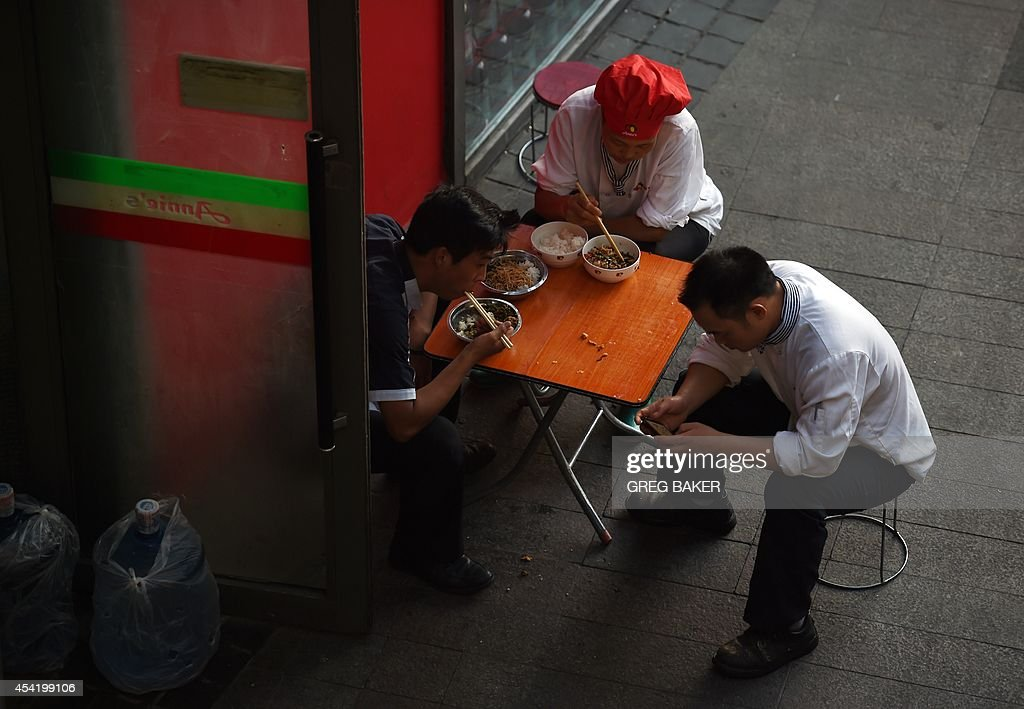 Restaurant workers eat dinner outside their establishment in Beijing on August 26, 2014. Foreign direct investment (FDI) into China dropped by more than a sixth year-on-year in July, the government said on August 18. AFP PHOTO / Greg BAKER