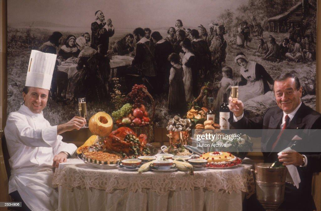 Restaurateur Sirio Maccioni and chef Daniel Boulud toast each other over a lavish spread at Maccioni's Le Cirque Restaurant, New York, 1990.