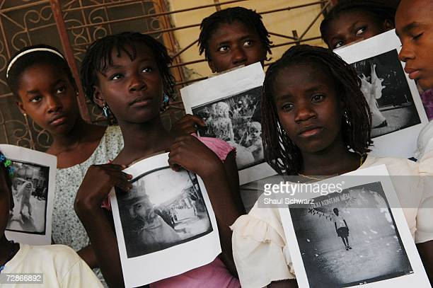 'Restavek' children display photographs they took for a class with photographer Gigi Cohen working in association with 'Kids With Cameras' who...