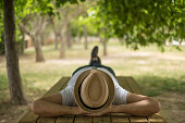 Restful boy wearing a straw hat laying down on a wooden table in the middle of the forrest at a park. You can put text on the background that is out of focus.