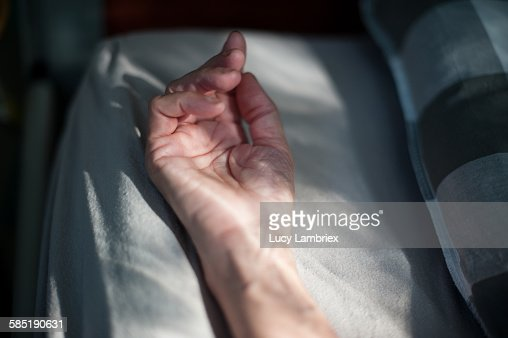 Resting hand in bed : Stockfoto