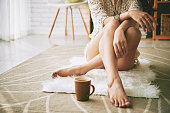 Legs of woman sitting on the floor with cup of coffee