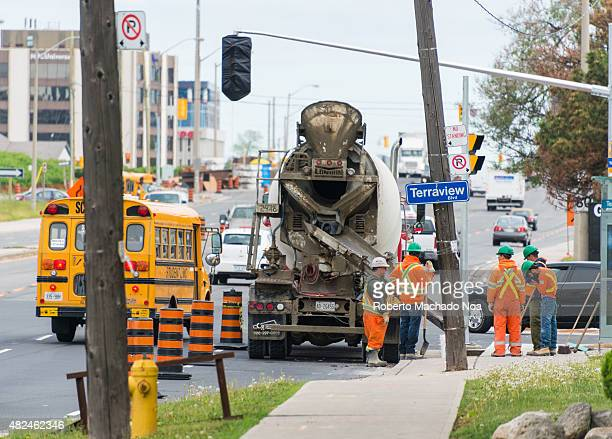 Restoration work on the Toronto city street Workers standing near mixer truck with concrete Vehicles driving on the road in the background