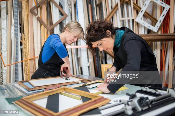 Restorer and framer laboratory craftswomen: Preparing frames