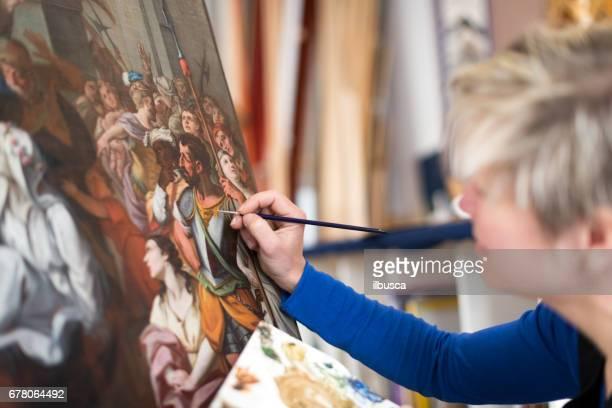 Restorer and framer laboratory craftswomen: Restoring antique religious painting canvas