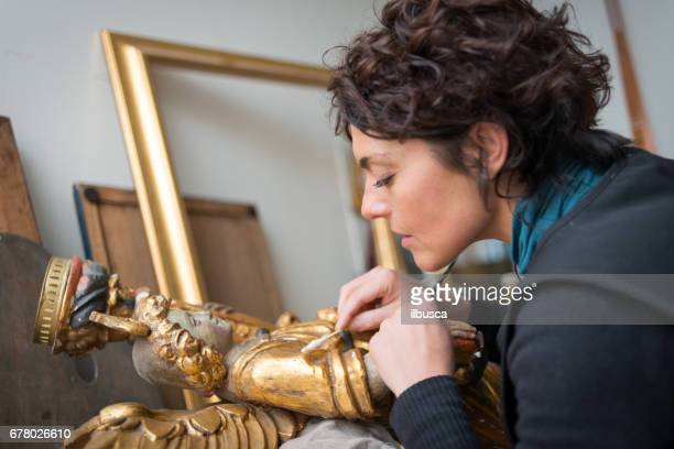 Restorer and framer laboratory craftswomen: Restoring antique golden angel statue