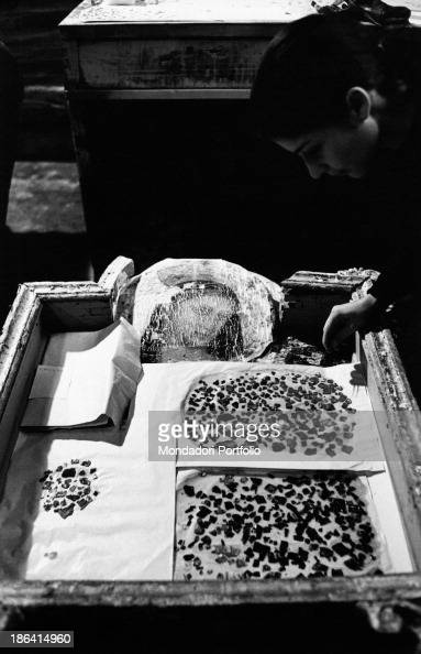A restorer checking the pieces come off from an altar piece damaged by the flood of the Arno River Florence November 1966