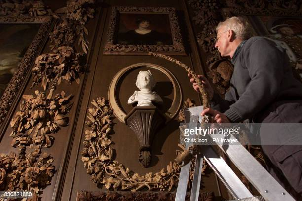 Restorer Graeme Dowling installs a newly carved wood frame to replace damaged 17th century works at the National Trust's Petworth House in West...