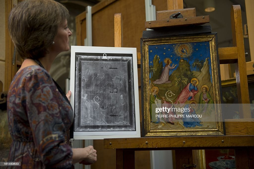 Restorer Maria Antonia Lopez de Asiain holds an x-ray of the painting 'Oracion en el huerto' (Agony in the Garden) supposedly by painter Colart de Laon next to the original restored painting at El Prado museum in Madrid on February 7, 2013. Spain's Prado art museum on February 11, 2013 unveiled a previously unseen jewel of French painting in which experts found a rare image of the historic French ruler Louis of Orleans. AFP PHOTO/ PIERRE-PHILIPPE MARCOU