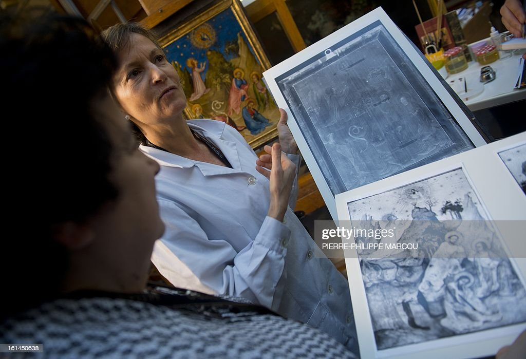 Restorer Maria Antonia Lopez de Asiain (back) holds an x-ray of the painting 'Oracion en el huerto' (Agony in the Garden) supposedly by painter Colart de Laon near the original restored painting at El Prado museum in Madrid on February 7, 2013. Spain's Prado art museum on February 11, 2013 unveiled a previously unseen jewel of French painting in which experts found a rare image of the historic French ruler Louis of Orleans.