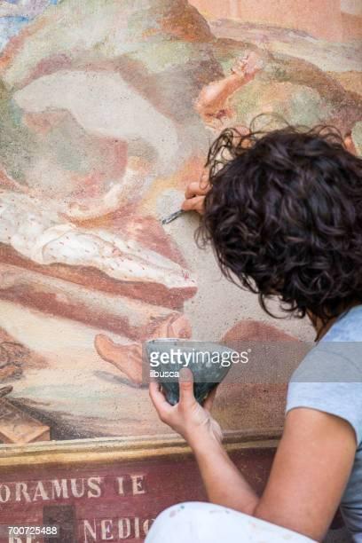 Restorer working on antique outdoor chapel fresco in Italy: Applying stucco plaster