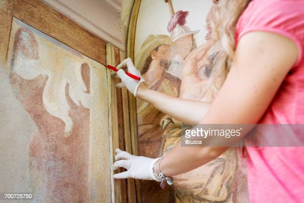 Restorer working on antique outdoor chapel fresco in Italy: Drawing lines
