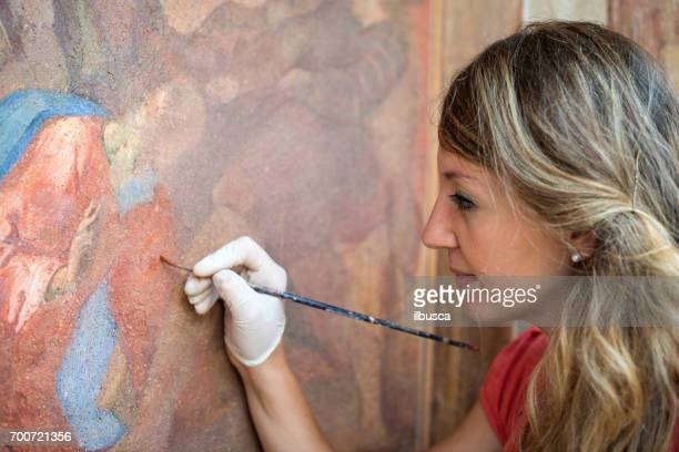 Restorer working on antique outdoor chapel fresco in Italy: Painting restoring of religious art