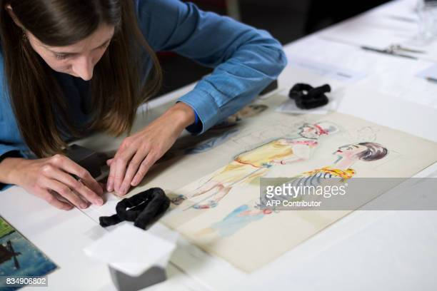 A restorer works on a drawing by German artist George Grosz from the collection of late German collector Cornelius Gurlitt during a press preview of...