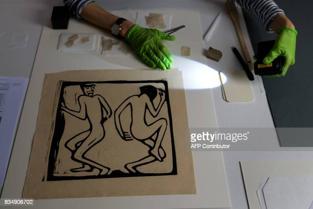 A restorer works on a masterpiece from the collection of late German collector Cornelius Gurlitt during a press preview of the restauration studio at...