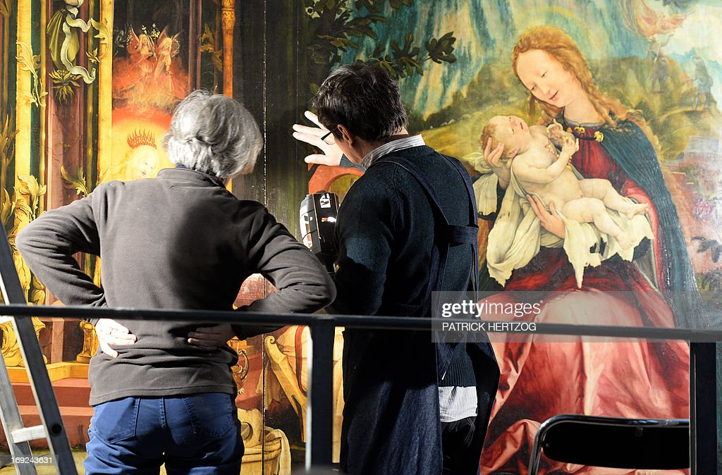 Restorers inspect the 'Isenheim Altarpiece' ('retable d'Issenheim' in French) by German Renaissance painter Matthias Grunewald, at the chapel of the Unterlinden museum in the eastern French city of Colmar, on May 22, 2013. A research team are studying if the 500-year old famed Renaissance religious work can be restored. AFP PHOTO / PATRICK HERTZOG