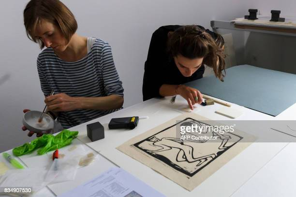 Restorers work on a masterpiece from the collection of late German collector Cornelius Gurlitt during a press preview of the restauration studio at...