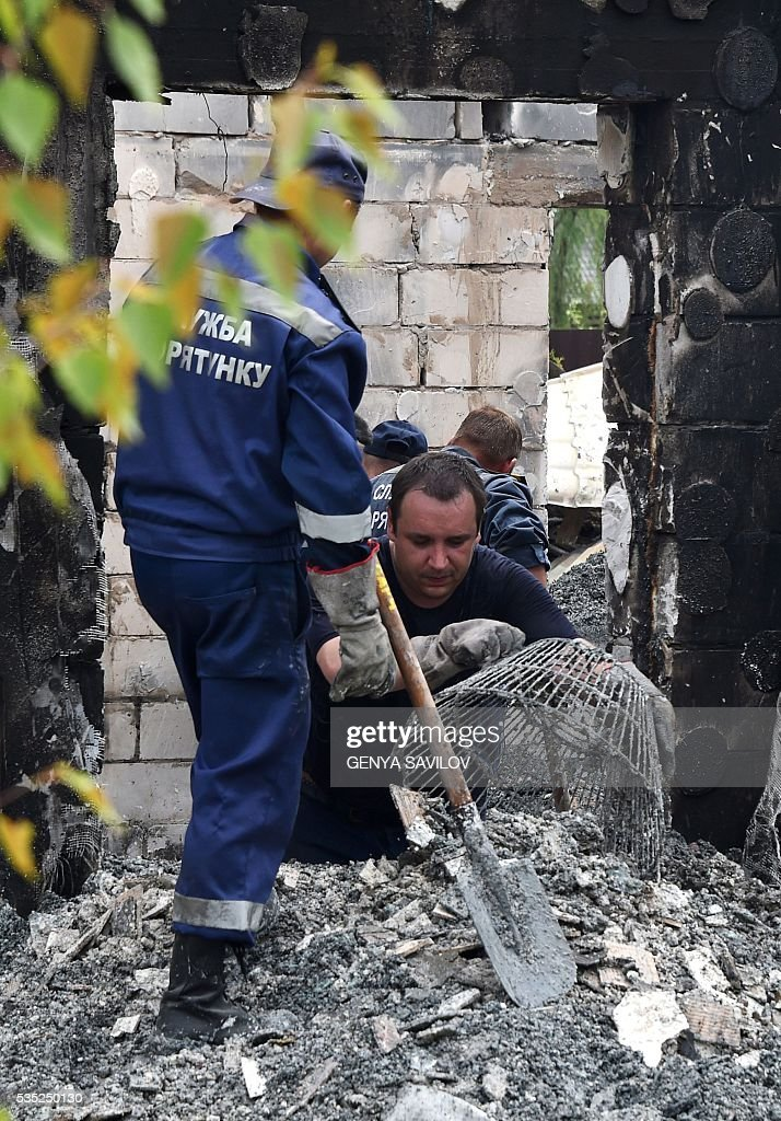 Resuce workers investigate the site of a fire in the village of Litochky, on May 29, 2016. Seventeen people died when a makeshift home for elderly people outside the Ukrainian capital Kiev caught fire in the early hours of May 29, the latest tragedy to shake the conflict-riven country. The fire tore through the two-storey shelter for the elderly which is in the village of Litochky, located some 50 kilometres (31 miles) north of Kiev. / AFP / GENYA