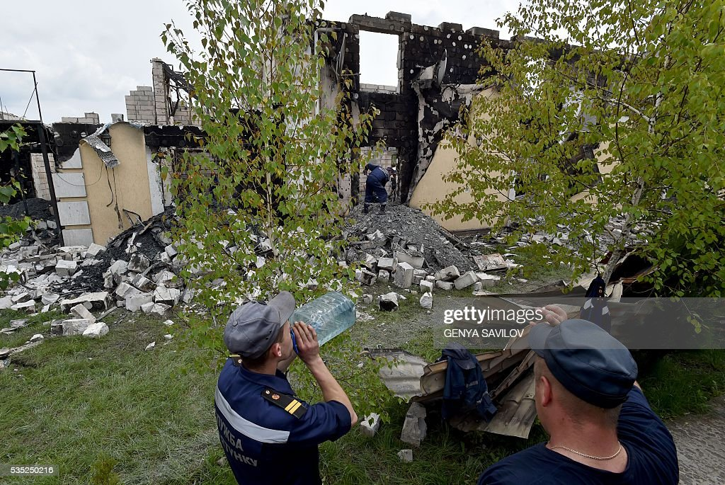 Resuce workers take a break during the investigation of the site of a fire in the village of Litochky, on May 29, 2016. Seventeen people died when a makeshift home for elderly people outside the Ukrainian capital Kiev caught fire in the early hours of May 29, the latest tragedy to shake the conflict-riven country. The fire tore through the two-storey shelter for the elderly which is in the village of Litochky, located some 50 kilometres (31 miles) north of Kiev. / AFP / GENYA