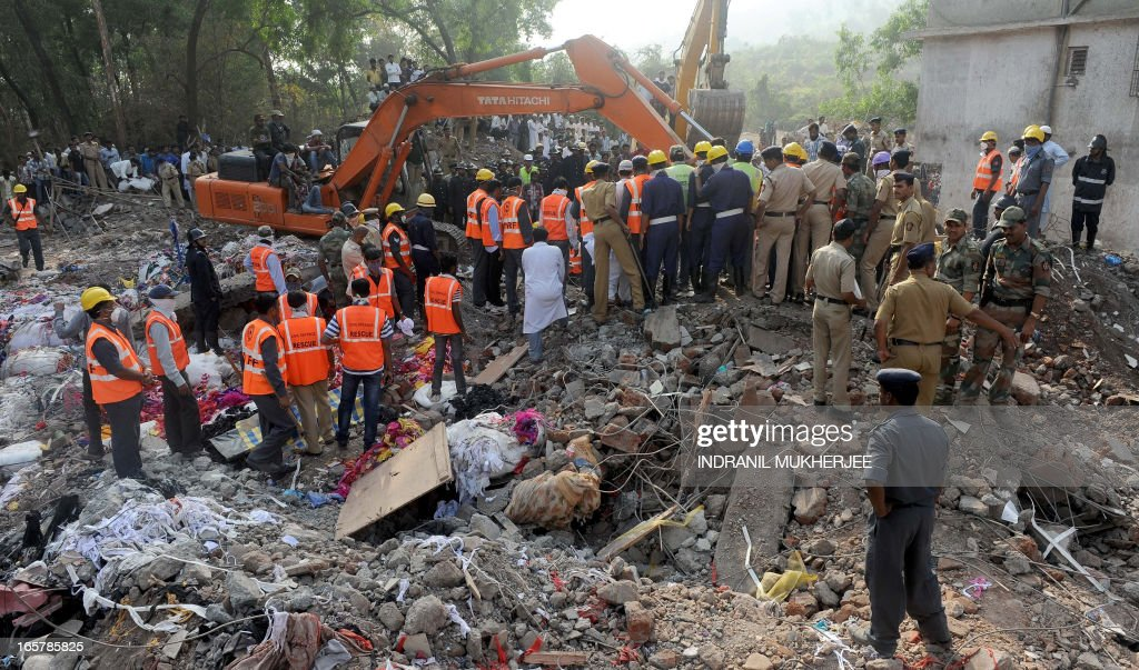 Resue officials and disaster management staff stand on top of the rubble and debris at the site of a building collapse at Mumbra in Thane, on the outskirts of Mumbai on April 6, 2013. The number of people killed when an unauthorised apartment block collapsed on the outskirts of Mumbai has risen to 72, police said Saturday, as bulldozers were brought in to help find survivors.