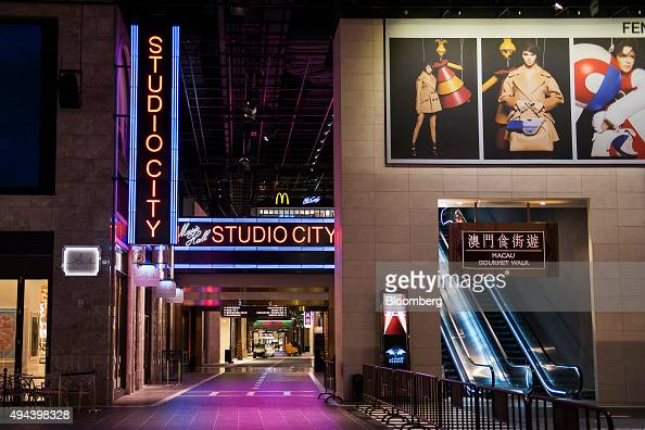 Retail outlets stand in The Boulevard as an escalator leads to Macau Gourmet Walk at the Studio City casino resort developed by Melco Crown...