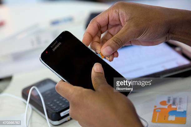 Retail sales consultant Salena Weekly inserts a SIM card into a newly purchased Samsung Electronics Co Galaxy S6 smartphone at an ATT store in...