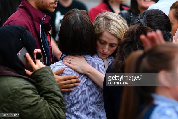 TOPSHOT Retail staff hug each other after being evacuated from the Arndale Centre shopping mall in Manchester northwest England on May 23 2017...