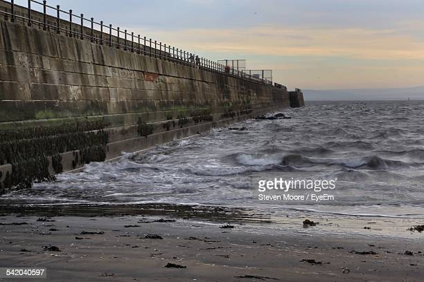 Retaining Wall At Sea Against Sky At Sunset