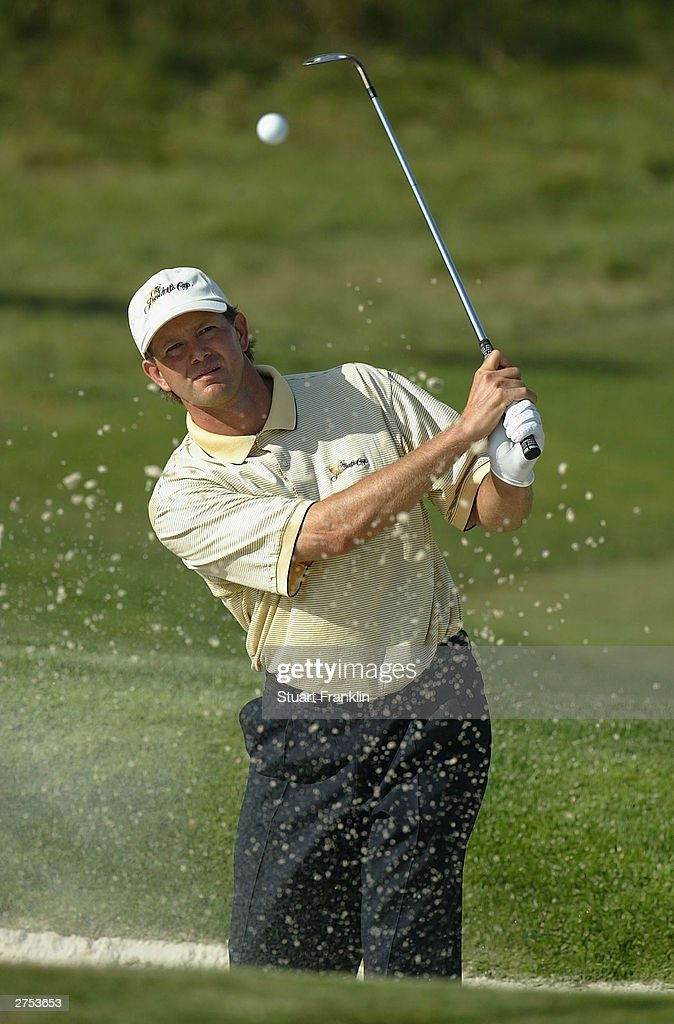 Retief Goosen of South Africa plays from a bunker on the 14th hole during his match against Tiger Woods and Charles Howell III of USA during the...