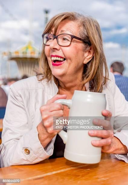 Retired active senior woman enjoys herself while drinking beer on Oktoberfest.