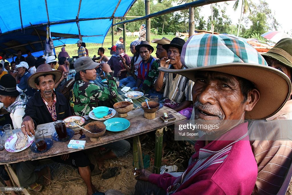 Retired and active jockeys gather at a coffee shop before a ''Pacu Jawi,'' a cow race, on November 17, 2012 in Batusangkar, Indonesia. The ''Pacu Jawi'' is held annually in muddy rice fields to celebrate the end of the harvest season. Jockeys grab the tails of the bulls and skate across the mud barefoot balancing on a wooden plank to show the strength of their bulls who are later auctioned to buyers.