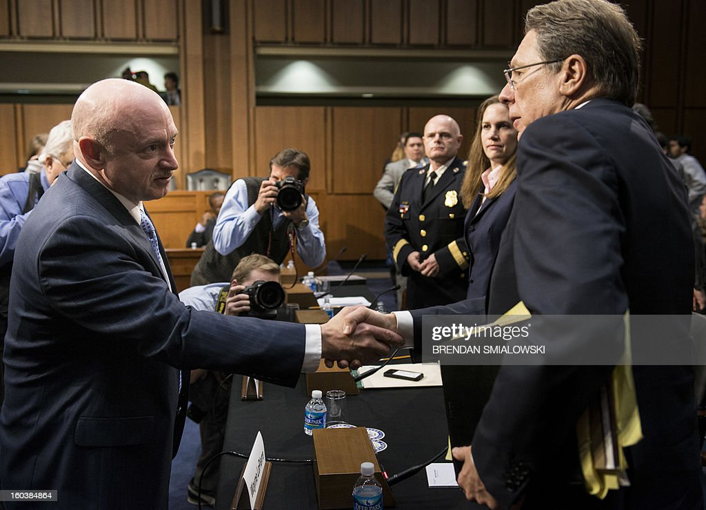 Retired Astronaut Mark Kelly (L), husband of former Arizona Rep. Gabrielle Giffords, shakes the hand of Wayne LaPierre, Chief Executive Officer of the National Rifle Association(NRA), after a hearing of the Senate Judiciary Committee on Capitol Hill January 30, 2013 in Washington, DC. The committee held the hearings to discuss solutions to gun violence in the United States. AFP PHOTO/Brendan SMIALOWSKI