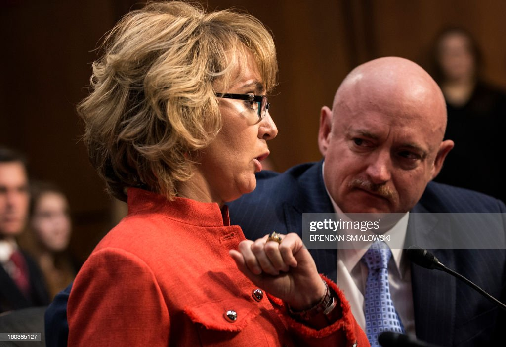 Retired Astronaut Mark Kelly, husband of former Arizona Rep. Gabrielle Giffords, listens as his wife makes a statement during a hearing of the Senate Judiciary Committee on Capitol Hill January 30, 2013 in Washington, DC. The committee held the hearings to discuss possible solutions to gun violence in the United States. AFP PHOTO/Brendan SMIALOWSKI