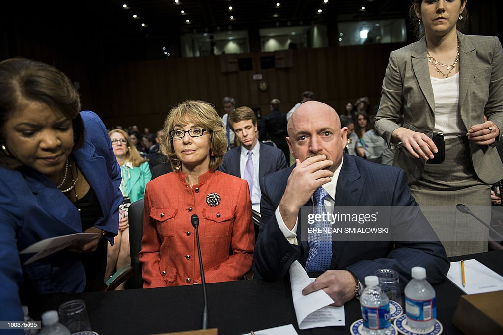 Retired Astronaut Mark Kelly, husband of former Rep. Gabrielle Giffords, sits with his wife, shooting victim former Rep. Gabrielle Giffords, before she makes a statement during a hearing of the Senate Judiciary Committee on Capitol Hill January 30, 2013 in Washington, DC. The committee held the hearing with Mark Kelly, Wayne LaPierre, Chief Executive Officer of the National Rifle Association, and others to testify about solutions to gun violence in the United States. AFP PHOTO/Brendan SMIALOWSKI